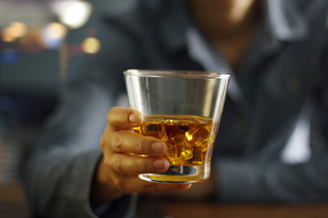 Close-up men holding whiskey drink alcoholic beverage at bar counter in the pub background