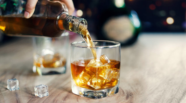 Man pouring whiskey into glasses, whisky drink alcoholic beverage with friends at bar counter in the pub.