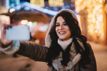 Beautiful smiled girl in winter coat standing in street and taking picture of her self. Christmas decoration in city streets. Winter evening.