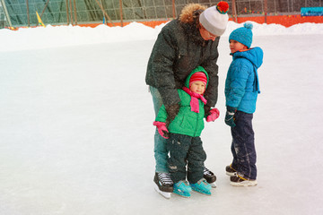 father with two kids- boy and girl- skating in winter