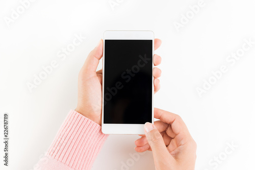 Woman Hand Holding White Mobile Phone Smartphone On White Table
