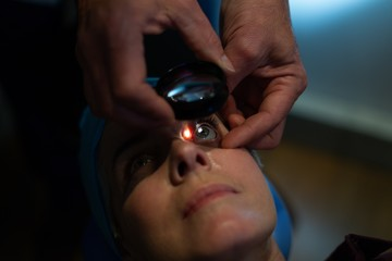 Optometrist examining patient eyes with eye test equipment in