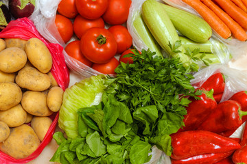 Close-up, Tomatoes, zucchini, carrots, potatoes, arugula, parsley, red pepper in plastic bags