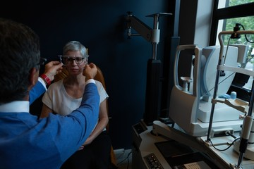 Optometrist examining patient eyes with eye test equipment