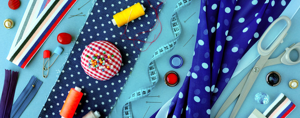 Panorama in the form of items for sewing. Fabric with a pattern of polka dots, measuring tape, tailoring scissors, thread and needles for sewing fashionable clothes. View from above.
