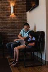 Father and daughter using digital tablet in dental clinic