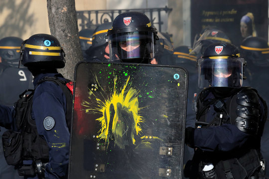Paint is splattered on the shield of a French CRS riot policeman as French CGT and Solidaires labour unions workers, students and retired people attend a demonstration to protest against the French government's reforms in Paris