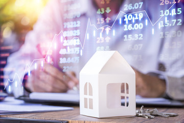 Businessman with model house and stock market chart background