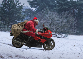 Santa Claus on red motorcycle with a sack driving along winter snow forest, delivery of gifts, Christmas concept