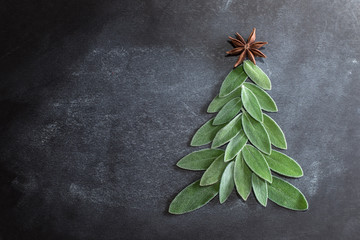 Fresh leaves of saffron lie on a dark background in the shape of a Christmas tree and anise star