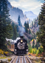 Steam Train Crossing a Trestle Bridge in the Mountains