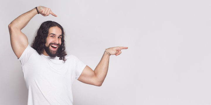 Portrait of strong bodybuilder man in white t-shirt with long wavy hair and beard, standing, looking at camera with toothy smile and pointing at light gray background copy space. indoor studio shot.