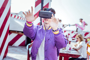 VR gadget. Pleased brunette keeping smile on his face while raising hands up