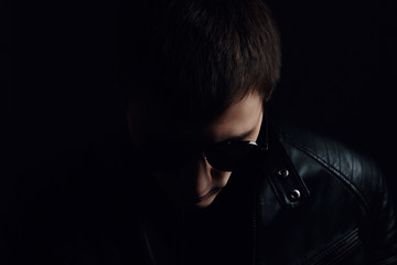 Young man's portrait. Close-up of serious young man in a black leather jacket and sunglasses on dark background. Confident concept
