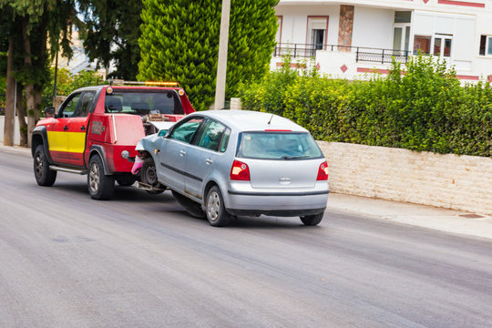 Crashed car being towed away by tow truck after accident