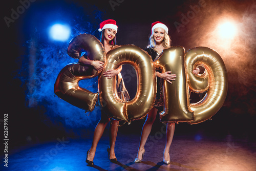 7bb46f94e421b two happy women in christmas hats holding sign 2019 made by golden balloons  on new year