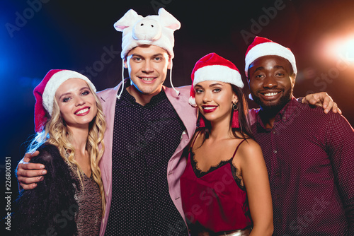 973afeca90293 smiling man in pig hat posing with multicultural friends in santa hats on  black with backlit