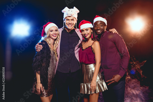 67f8f591c8257 cheerful man in pig hat posing with multicultural friends in santa hats on  black with backlit