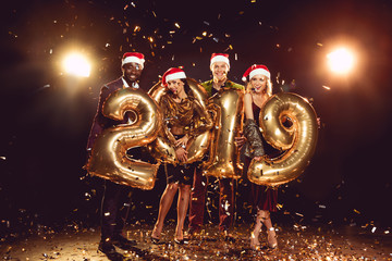 0467c8bd079ad beautiful friends in santa hats holding 2019 new year golden balloons and  standing on confetti with
