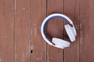 Musical equipment - White wireless headphone wooden background