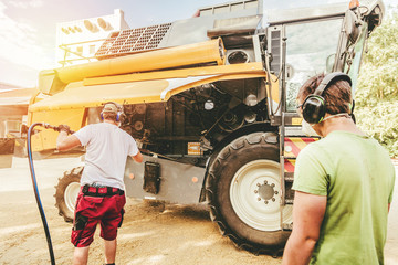The mechanics repair the yellow combine harvester in the farm yard.