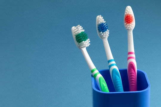 three toothbrushes stand in a cup