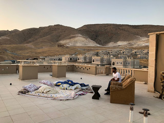 Mazlum Cetin sits on the roof of the apartment building where he lives with his family in new Hasankey