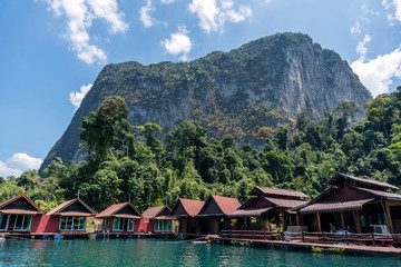 Wooden Thai traditional floating houses on a lake with mountains and rain forest in the background during a sunny day at Ratchaprapha Dam at Khao Sok National Park, Thailand