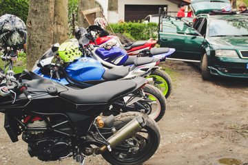 Sports motorcycles are near the house. The blue, red and black motobike. Hangover bikers