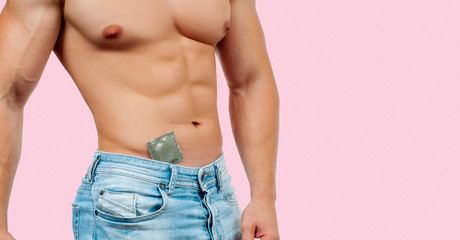 Handsome muscular man with condom on pink background