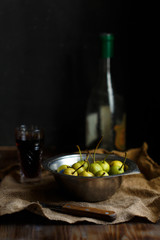 Wild pear in a metal bowl glass and bottle of pear wine on a wooden dark background. Rustic concept