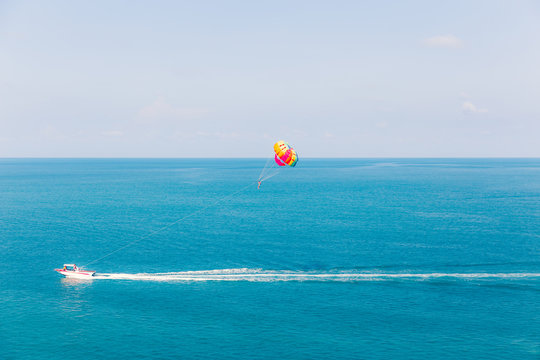 Parasailing at Chaweng Beach in Samui - Thailand extreme Sport. Tourists parasailing - popular entertainment for holiday travelers on Chaweng Beach in Samui, Thailand.