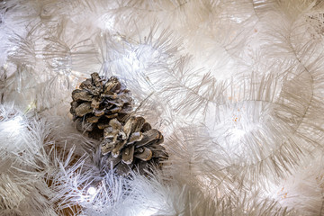 Christmas composition of white jewelry. Tinsel, cones, lanterns and candles. White Christmas snow. Shiny holiday decorations in warm soft light with wax candles. Picture of magic night