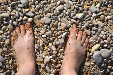 women's feet close-up on sea pebbles