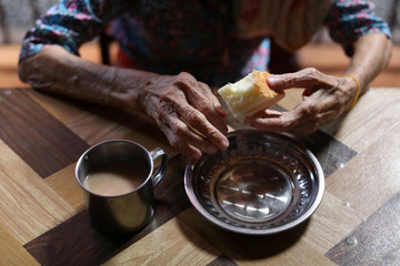 A resident eats a cake during tea break time at the Little Sisters of The Poor Home for The Aged Poor in Yangon