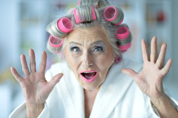 Portrait of a senior woman in bathrobe with curlers