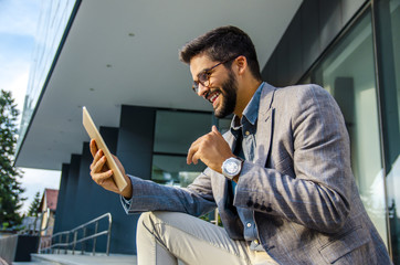 Happy young adult man in suit in front of office looking happily at digital tablet