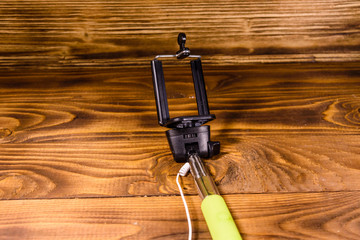 Selfie stick with adjustable clamp on a wooden table