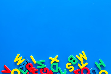 Alphabet for kids concept. English letters in disorder on blue background top view copy space