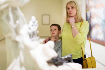 Mother and son looking at classical statues