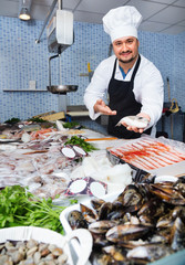 Seller in white cap and black apron showing counter with fish