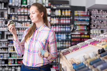 woman customer holding glass jar with color paint in art department