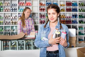 Portrait of  girl choosing paint color in aerosol can in art shop