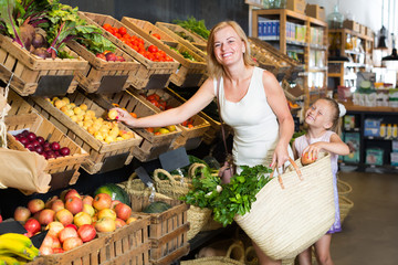 female customer with daughter choosing fruits.