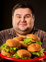 Hamburger eating fast food contest. Junk meal leads to obesity. Person regularly overeats. Binge eating.