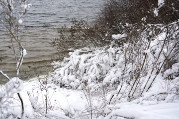 Snowy river bank. Winter river. A winter river landscape with snow-covered banks.