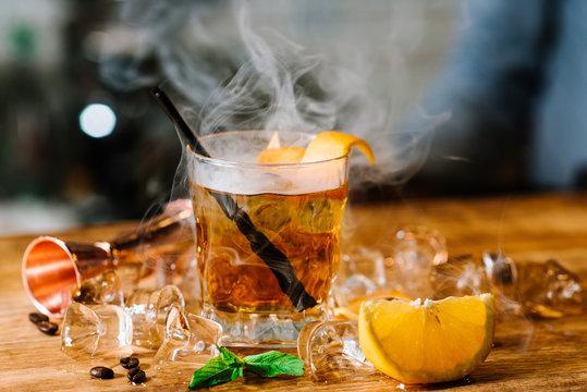 Whiskey cocktail with a smoke called smoking gun at the bar