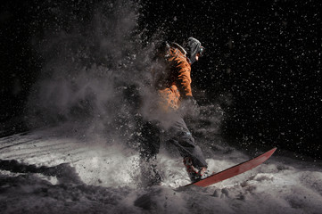 Male snowboarder riding on board on a powder snow