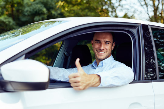 A young man sitting in a car showing thumb up