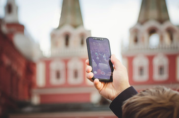 A tourist man is taking pictures on the phone in Red Square in Moscow.